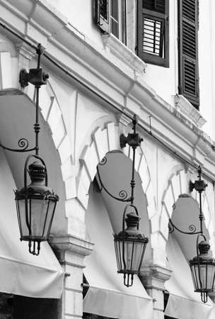 kerkyra: Greece. Corfu (Kerkyra) island. Corfu town. Street lamp detail at an open-air cafe. In black and white Stock Photo