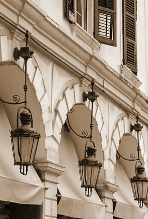 kerkyra: Greece. Corfu (Kerkyra) island. Corfu town. Street lamp detail at an open-air cafe. In sepia toned