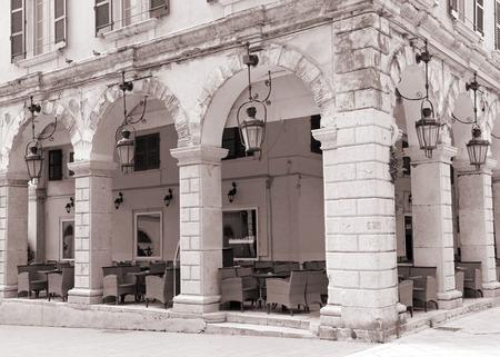 kerkyra: Greece. Corfu (Kerkyra) island. Corfu town. An open-air cafe. In sepia toned Stock Photo