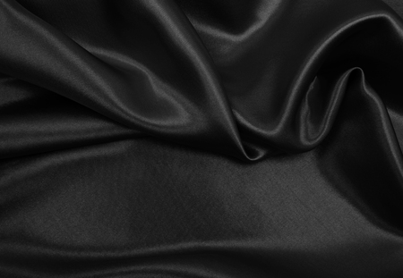 Smooth elegant black silk or satin texture can use as abstract background. Luxurious background design