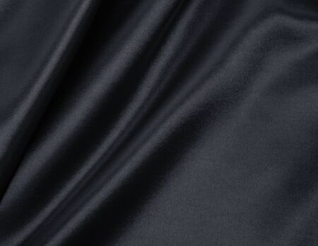 Smooth elegant dark grey silk or satin texture can use as abstract background. Luxurious background design