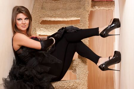 Beautiful young woman in high heels shoes sitting on stairs photo