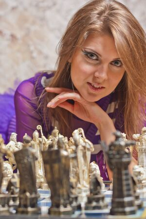 Beautiful young woman lying on floor and playing chess Stock Photo - 18206034