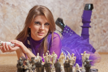 Beautiful young woman lying on floor and playing chess Stock Photo - 18206022