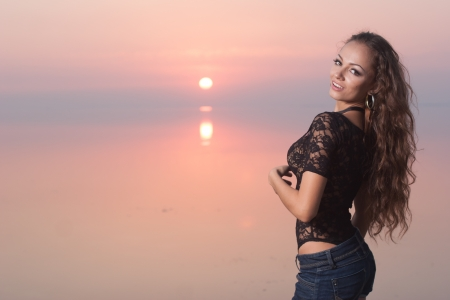 Sexy beautiful woman in jeans shorts on the beach at sunset photo