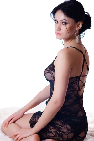 Sexy young brunette in black negligee sitting on the fur photo