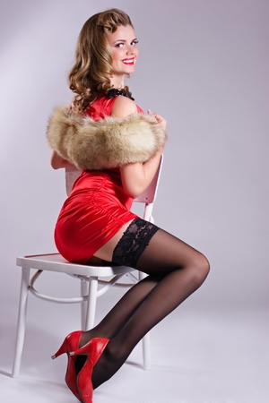 Pin up girl in red dress and red shoes sitting on the chair photo