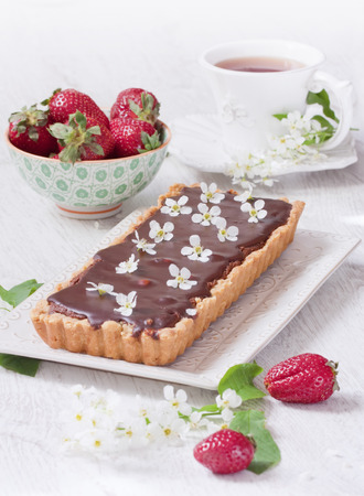 Chocolate tart with strawberry and branch of bird-cherry photo