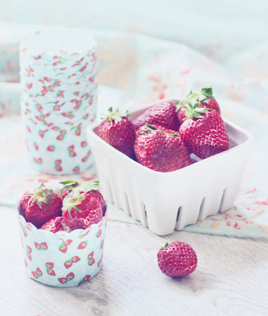 Fresh ripe strawberries on a paper case and white basket photo