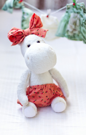 White hippopotamus toy with orange bow on a white bachground photo