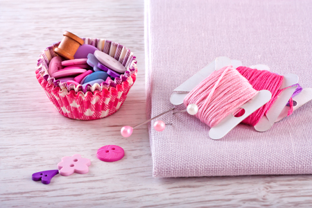 Sewing kit with a check fabrics, buttons, thread and pins
