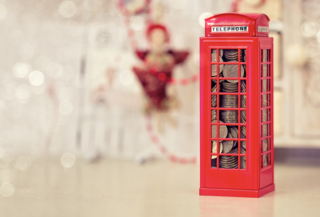 London telephone booth moneybox on wooden white grunge table photo