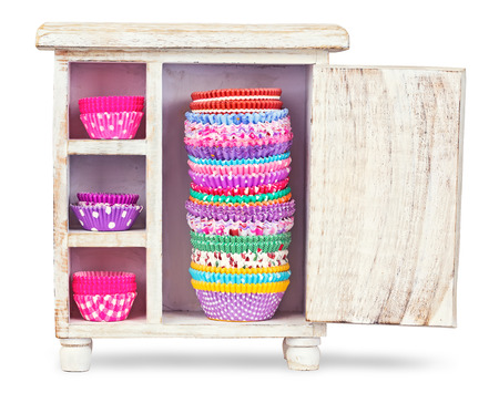 Colorful forms to make cupcakes from paper on a wooden box isolated photo