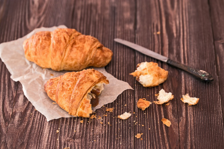 croissant and crumbs for breakfast on a dark wooden table photo