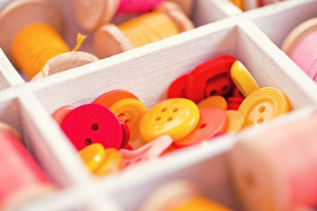 red pink: yellow, red, pink  buttons  arranged in a white wooden box Stock Photo