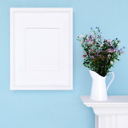 marcos cuadros: Maqueta marco vacío y flores silvestres en el fondo azul de la pared Foto de archivo