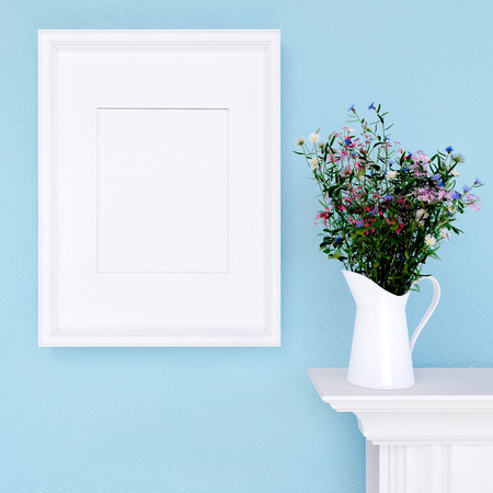 decor: Mock up empty frame and wildflowers on  blue wall background Stock Photo
