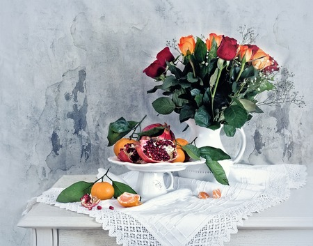 Still life with red pomegranate, orange tangerines and color roses Stock Photo