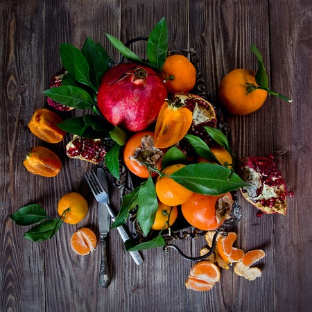 wood cut: Fresh fruits on a wooden background. Raw and vegetarian eating frame. Sliced orange, persimmon, tangerine, pomegranate.  Fruit set. Top view Stock Photo