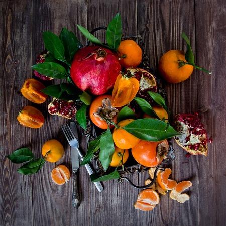 tropisch: Frische Früchte auf einem hölzernen Hintergrund. Raw und vegetarische Ernährung Rahmen. Geschnittene Orange, Persimmon, Mandarine, Granatapfel. Obst-Set. Aufsicht