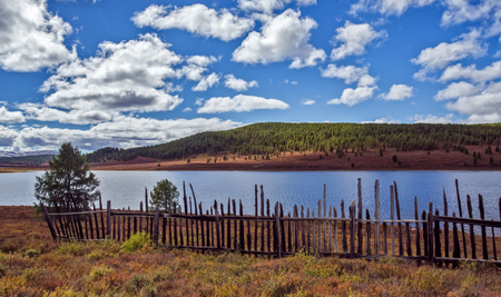 ulagan: vintage fence near lake lake in the vicinity of the mountain pass Ulaganskiy. Altai, Russia