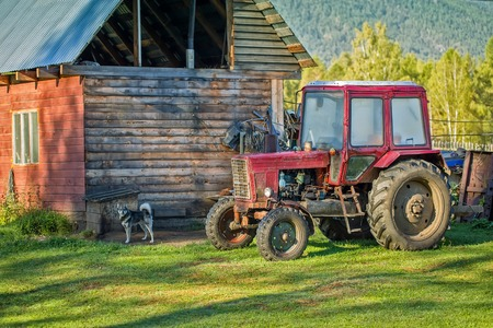 vintage landscape: Old red rusted tractor stay near house and dog near the box Stock Photo