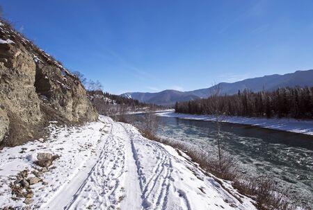 katun: Snowy Mountain road along the river Katun, Russia, Siberia Altai Stock Photo