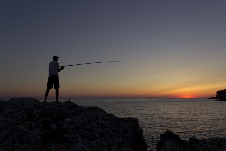 Sea fisherman at sunset Stock Photo