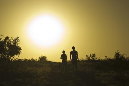 L'homme et l'enfant avec un chien au coucher du soleil Banque d'images