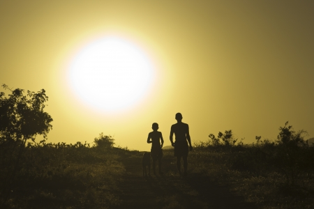 Man and child with dog at sunset Stock Photo
