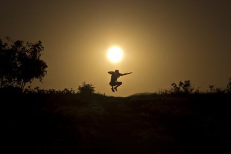 L'homme sautant sur le fond de la magnifique coucher de soleil Banque d'images