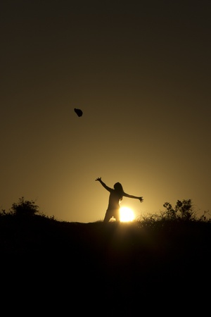 Girl makes the graceful throw at sunset