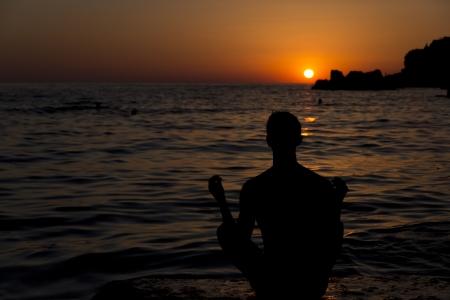 L'homme m�ditant par la mer au coucher du soleil Banque d'images