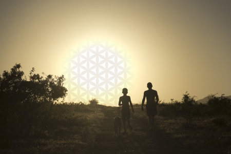 Man and child walking the dog at sunset in the form of the flower of life Stock Photo - 18597284