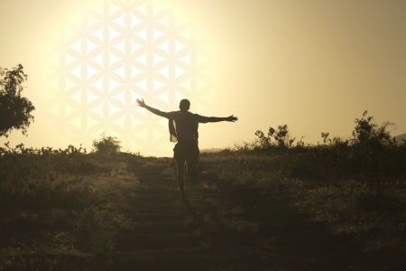 Man running toward the setting sun in the form of flower of life Stock Photo