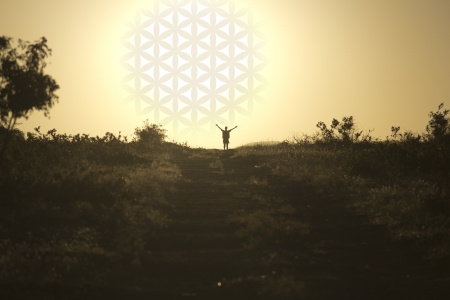 The man standing with his hands up near the setting sun with flower of life
