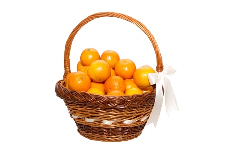 Christmas tangerines on white background in the wooden basket