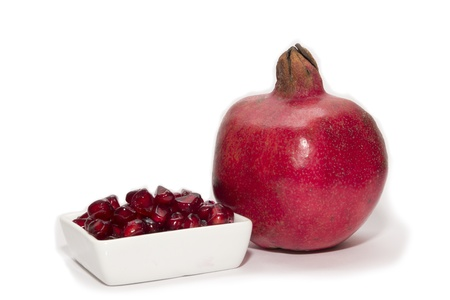 Red ripe pomegranate whole and in the plate on white background