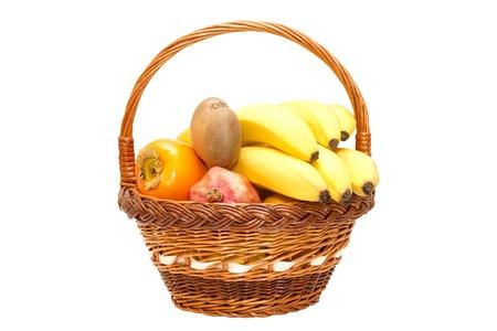 Grenades fruits, bananes, kiwis, kakis dans le panier Banque d'images