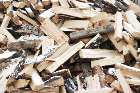 Beaucoup de rondins de bois dans le tas de neige-couvert
