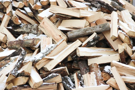 Many wooden logs in the pile of snow-covered Stock Photo