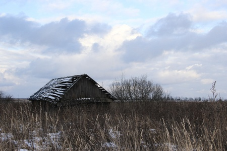 Old broken-down wooden house stands in the field