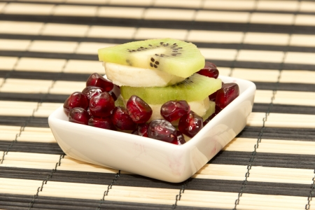 Pieces of fruit banana, kiwi, pomegranate in the small platter