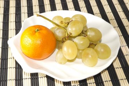 Le mandarin et le raisin sur la plaque en forme de coquilles Banque d'images