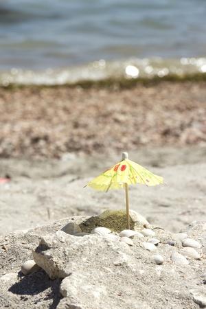 Small paper umbrella on the beach near the sea shells