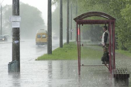 UOMO pioggia: L'uomo in piedi alla fermata dell'autobus sotto la pioggia battente Archivio Fotografico
