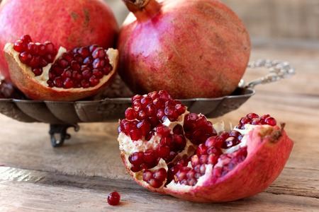 red juicy pomegranate on plate lying on wooden table from old boards Stock fotó