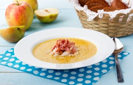 potage: Indian soup Potage Mulligatawny with apple curry, bacon and basil in white soup bowl on blue desk with polka dot napkin
