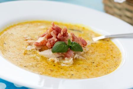 potage: Sopa india Potage Mulligatawny con curry, tocino y albahaca en un taz�n blanco sopa en la mesa azul con servilleta de lunares