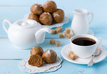 brown buns on blue wooden table with coffee cup, sugar, coffee pot and milk jug photo